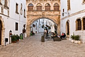 View of archway with people sitting at cafe in Ostuni, Italy