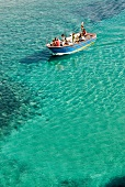 Elevated view of people in boat on the turquoise water, Italy