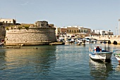 View of boats, houses, bridge and harbour wall at port of Gallipoli, Italy