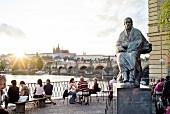 People sitting near Smetana Memorial at sunset, Prague