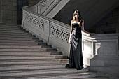 Frau im Abendkleid, steht auf der Treppe
