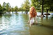 Rothaarige Frau steht im Wasser Wasser, von hinten
