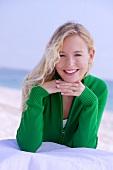 Blonde Frau in grüner Strickjacke , Kinn auf den Händen abgestützt