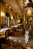 Tables laid in the restaurant Le Cinq at the Four Seasons George in Paris, France