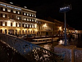 View of illuminated hotel facade at night, bridge and canal