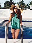 Frau mit großem Strohhut, Sonnenbrille, grünes Hemd steigt in Pool