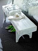Weissgestrichene Bettbank aus Holz als Ablagemöglichkeit
