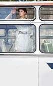 Frau in Sommerkleid, steht in Bus, blickt aus dem Fenster, traurig