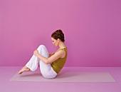 Pilates - Rolling like a Ball: Frau sitzt, Knie anziehen, Step 1