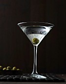 A Martini with an olive in a stemmed glass