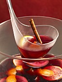 Feuerzangenbowle (mulled wine with added rum and sugar) with a cinnamon stick, lemons and oranges