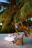 Tables laid on beach at dusk in Veligandu Island Resort, Maldives
