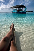 Close-up of legs in shallow water and boat in Veliganduhuraa island, Maldives