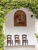 Three chairs under religious icon in chapel on Pelion Mountain, Eastern Magnesia, Greece