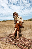 Frau sitzt in afrikanischer Steppe mit Löwenbaby auf dem Schoß