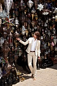 Smart looking woman wearing beige suit looking at oriental lamps in front of shop