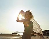 Frau am Strand, Abendsonne, Schal, in Bewegung, Kamerablick
