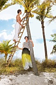 Man climbing ladder to pick coconuts from tree, woman holding ladder below the tree