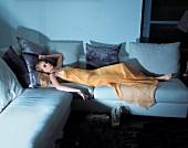 Blonde Frau im Abendkleid liegt auf einem Sofa