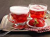 Two glasses of strawberry punch with ice cubes and fresh strawberries
