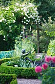 Skulptur vom Flötenspieler im sommerlichen Garten
