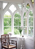 Table and chair in front of white colonial window at Rieseby, Germany