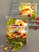 Egg salad at with pomegranate seeds served in jars on beds of lettuce