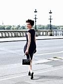 Frau in auberginefarbenen Etuikleid geht über eine Straße