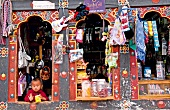 Child looking through window of shop, Bhutan