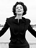 Frau brünett, Kostüm schwarz, 60er- Jahre-Stil, Kamerablick, s/w