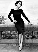 Frau brünett, Kleid, 60er-Jahre-Stil Hand an Taille, Blick seitlich, s/w