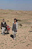 Woman wearing gray sweater and pants walking with man with donkey in desert