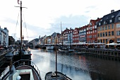 View of colourful buildings along with boats in Nyhavn at dusk, Copenhagen, Denmark