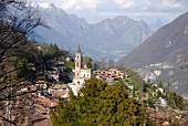 View of cityscape of Ticino with houses, church and mountain range, Switzerland