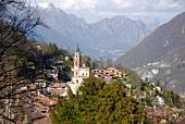 Tessin: Stadtansicht Carona, Kirche, Häuser, Tal, Berge, idyllisch.