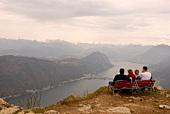 People sitting on beach at Monte San Giorgio in Lugano, Switzerland