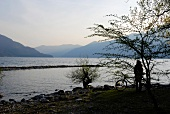 View of man with cycle at Ascona mountain range and lake at dusk in Ticino, Switzerland