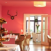 View of Hotel Haus Hirt Restaurant with tables, red wall and wicker chairs, Austria