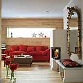 Wooden wall, red sofa and fire place in living room, Austria