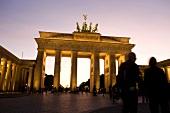 Berlin: Pariser Platz, Brandenburger Tor, abends, Menschen, unscharf.