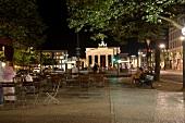 Berlin: Pariser Platz, Menschen, Ti- sche, Brandenburger Tor, abends.