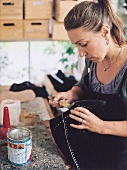 Shoemaker Anja Hoffmann applying glue on shoe sole