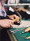 Shoemaker Anja Hoffmann holding hammer while preparing shoe