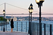 Rear view of woman standing near sea, overlooking city at sunset, Istanbul, Turkey