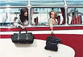 Woman and child holding travel bags out of bus window, smiling while looking at each other