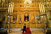 Woman kneeling and worshipping in Hagios Georgios church in Istanbul, Turkey