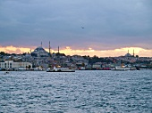 View of cityscape of city on coast of Bosphorus and ferryboats at dusk, Istanbul, Turkey