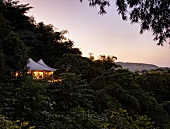 View of illuminated Chiang Saen Luxury Hotel and rainforest at dusk, Thailand