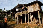 Man walking on road with huts on side in village at Ban Palai, Thailand