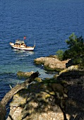 View of fishing boat in sea and rocky coast, Turkey